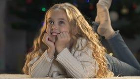 Niña linda que sueña sobre los regalos y la celebración alegre de la Navidad, alegría almacen de metraje de vídeo