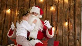 Niña linda que tira de la barba del ` s de Papá Noel para comprobar si él sentada real del ` s en su revestimiento almacen de video