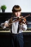Niña linda que toca el violín y ejercicio interior Fotografía de archivo libre de regalías