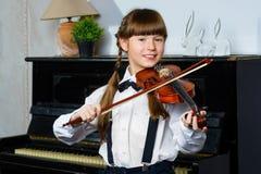 Niña linda que toca el violín y ejercicio interior Imagenes de archivo