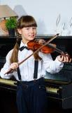 Niña linda que toca el violín y ejercicio interior Fotografía de archivo