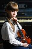 Niña linda que toca el violín y ejercicio interior Foto de archivo