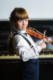 Niña linda que toca el violín y ejercicio interior Foto de archivo libre de regalías