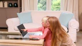 Niña linda que usa el ordenador portátil con la madre almacen de video