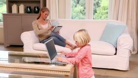 Niña linda que usa el ordenador portátil mientras que tableta de las aplicaciones de la madre metrajes