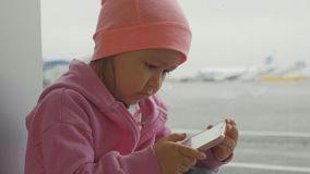 Niña linda que usa el teléfono elegante en el aeropuerto, cámara lenta del primer metrajes