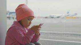 Niña linda que usa el teléfono elegante en el aeropuerto, cámara lenta del primer almacen de metraje de vídeo