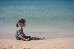 Niña linda sola que se sienta en la playa de la arena imagen de archivo