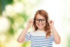 Niña linda sonriente con las lentes negras Foto de archivo