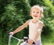 Niña linda sonriente con su bicicleta Imagenes de archivo