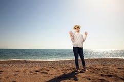 Niña linda sonriente que camina en la playa imagenes de archivo