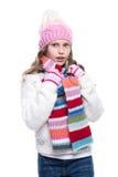 Niña linda sonriente que lleva el suéter hecho punto y la bufanda colorida, sombrero, manoplas aisladas en el fondo blanco Ropa d Imagenes de archivo