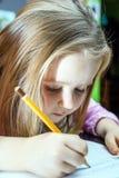 Niña linda studing a hablar y a escribir letras en casa Fotos de archivo