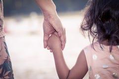 Niña linda y madre del niño que mantienen la mano unida Imagen de archivo