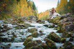 Niña linda y madre que se sientan en una roca en bosque del otoño en la corriente Imagenes de archivo
