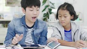 Niña linda y muchacho joven que juegan en videojuego competitivo en smartphones y la tableta, almacen de metraje de vídeo