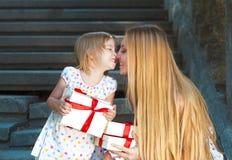 Niña linda y sus presentes de la tenencia de la madre Foto de archivo libre de regalías