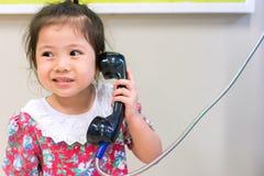 Niña linda y teléfono viejo Fotografía de archivo