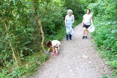 Niña, madre embarazada y abuela limpiando el bosque de plásticos fotos de archivo