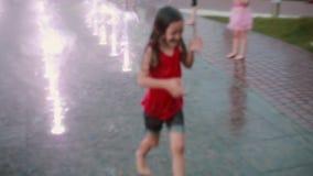 Niña mojada que corre a través de los chorros de agua en la fuente y la risa Niño que se divierte en día de verano caliente almacen de metraje de vídeo