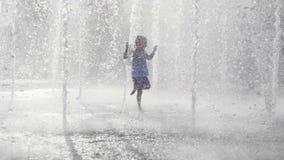 Niña mojada que funciona con y que se divierte en la fuente del jet en el parque público de la ciudad almacen de metraje de vídeo