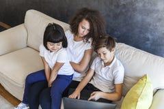 Niña, muchacho adolescente y ordenador portátil del wirh de la muchacha del pelo rizado en el sofá a Imágenes de archivo libres de regalías