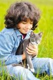 Niña muy linda con el gato en prado Foto de archivo