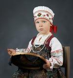 Niña orgullosa en el sarafan ruso tradicional durante el bordado imagen de archivo