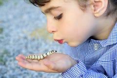 Niña palying con el gusano de seda en manos Foto de archivo