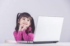 Niña pensativa delante de un ordenador portátil Imágenes de archivo libres de regalías