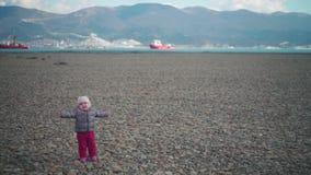 Niña pequeña adorable en sombrero y chaqueta en la playa en un día de primavera soleado almacen de video