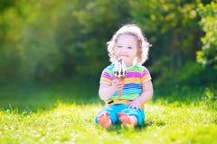 Niña pequeña adorable que come el helado en un jardín Imagen de archivo