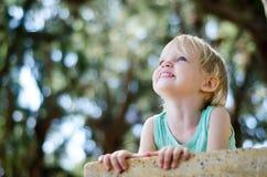 Niña pequeña adorable que mira para arriba sobre el foco bajo de la cámara Imagenes de archivo