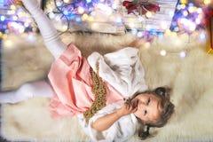 Niña pequeña bonita liying cerca de adornar el interior de la Navidad Fotografía de archivo