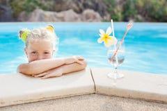 Niña pequeña con el cóctel en piscina tropical de la playa Foto de archivo