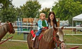 Niña pequeña con la mamá primero Pony Ride Fotos de archivo libres de regalías