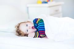 Niña pequeña de bostezo divertida que despierta por mañana Foto de archivo
