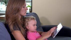 Niña pequeña de enseñanza de la mujer de la madre que usa la tableta almacen de metraje de vídeo