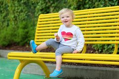 Niña pequeña de risa que come el helado al aire libre Fotografía de archivo