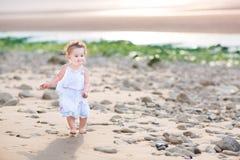 Niña pequeña divertida que corre en la playa en la puesta del sol Foto de archivo