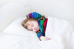 Niña pequeña divertida que duerme en una cama blanca imagenes de archivo