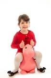 Niña pequeña dulce que juega con un isolat de salto del juguete del caballo de la felpa imagen de archivo