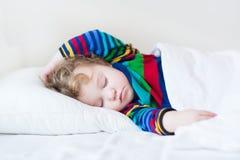 Niña pequeña durmiente divertida en una cama blanca foto de archivo