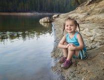 Niña pequeña en el borde del ` s del lago imágenes de archivo libres de regalías