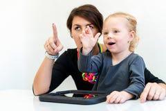 Niña pequeña en la sesión de terapia profesional del niño que hace ejercicios juguetones sensoriales con su terapeuta foto de archivo libre de regalías