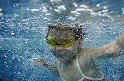 Niña pequeña feliz divertida que nada bajo el agua en a Fotos de archivo libres de regalías