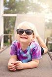 Niña pequeña feliz linda que sonríe como ella pone afuera por la piscina, fotos de archivo libres de regalías