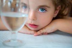 Niña pequeña grande de los ojos azules que mira la cámara de una taza del agua foto de archivo libre de regalías