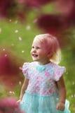 Niña pequeña joven hermosa que sonríe como caída de pétalos de la flor de a Fotos de archivo