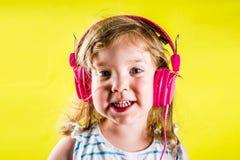 Niña pequeña linda con los auriculares Imagen de archivo